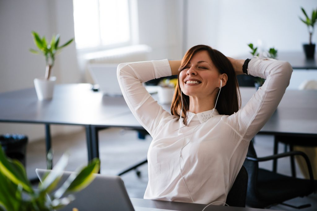 happy woman in the office with earphones