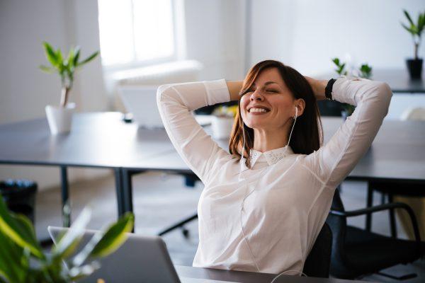 uśmiechnięta kobieta w biurze w słuchawkach